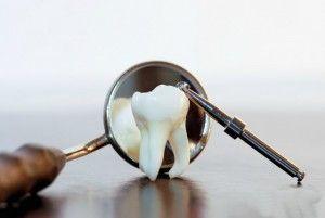 зуб и стоматологическое зеркальце