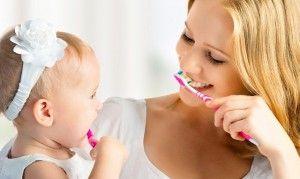 мама и девочка чистят зубы